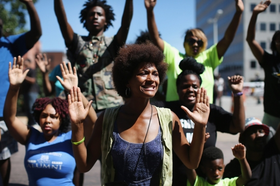 "Demonstrators raise their hands and chant ""hands up, don't shoot"" during a protest over the killing of Michael Brown on Aug. 12 in Clayton, Mo."